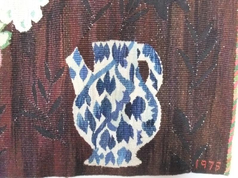 Ann-Mari Forsberg, detail of Swenske Örtekrantz tapestry with blue and white ceramic pitcher in lower right hand corner and date of 1975.